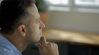 CU SELECTIVE FOCUS Man sits in office with hand under chin, thinking / Singapore