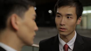 CU SELECTIVE FOCUS Two business man talking on street at night / China