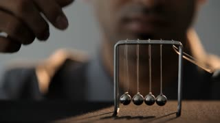 CU SELECTIVE FOCUS Young man playing with Newton's cradle on desk