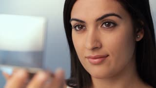 CU SELECTIVE FOCUS Young woman applying mascara to eyelashes, studio shot