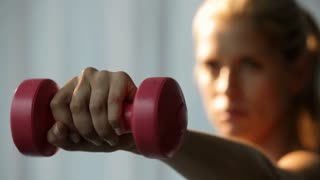 CU SELECTIVE FOCUS Young woman exercising with dumbbells