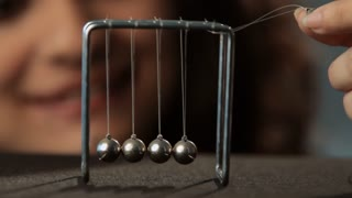 CU SELECTIVE FOCUS Young woman playing with Newton's cradle