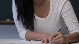 CU TU Young woman writing at desk in classroom