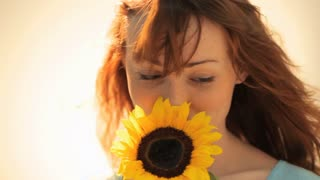 CU Woman with Red Hair Holding Sunflower and Smiling