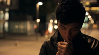 CU Young man walking and smoking cigarette on street at night / China