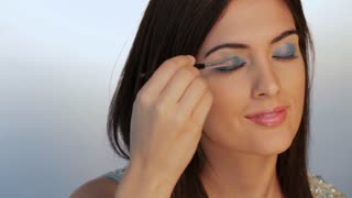 CU Young woman applying eye shadow, studio shot