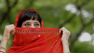 CU Young woman holding sari against face then smiling