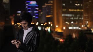 Man playing games on mobile phone and smiling with city lights in background at night/ Beijing, China