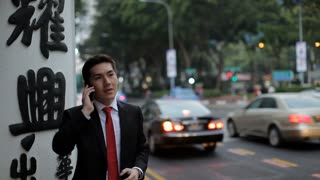 MH Businessman Standing by Busy Street Talking on Phone / Singapore