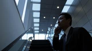 MH LA Businessman Talking on Phone While Riding Escalator / Singapore