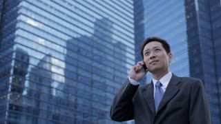 MH LA LD Businessman Talking on Phone in front of Modern Buildings / Singapore
