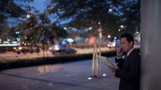 MH LD Businessman Reading Newspaper and Talking on Phone on Street at Night / Singapore
