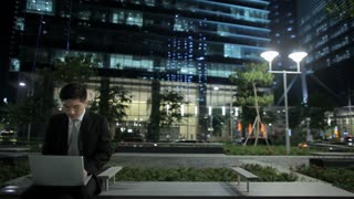 MH LD Businessman Sitting on Bench in front of Buildings, Working on Laptop at Night / Singapore