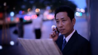 MH LD Businessman Standing on Street Holding Newspaper and Talking on Phone at Night / Singapore