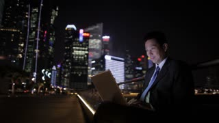 MH LD Businessman Working on Laptop at Night with City Skyline in Background / Singapore