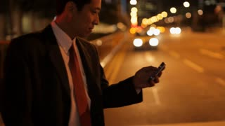 MH TS Businessman Crossing Street While Texting on Phone at Night / Singapore