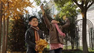 MS Boy and girl jumping and throwing dry leaves in park / China
