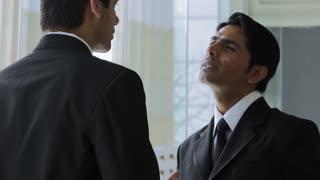 MS Businessmen talking in office lobby / Singapore