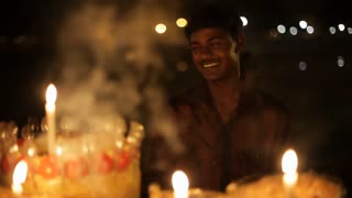 MS Candles burning in foreground, young man smiling in background / New Delhi, India