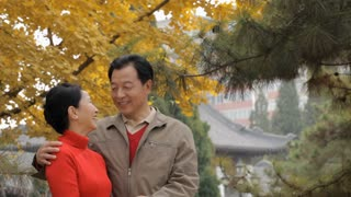 MS Elderly couple laughing and talking, standing in park / China