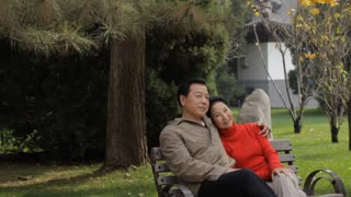 MS Elderly couple sitting and embracing on park bench / China
