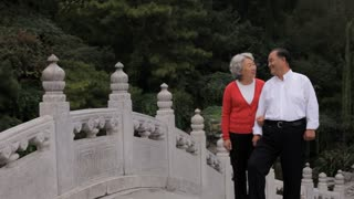 MS Elderly couple standing on stone bridge, smiling / China