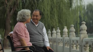 MS Elderly couple talking and laughing, sitting on park bench /Beijing, China