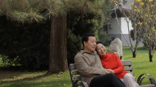 MS Elderly couple talking, sitting and embracing on park bench / China