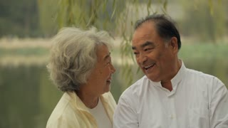 MS Elderly couple talking together in a park / China