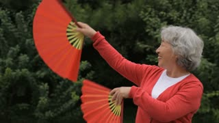 MS Elderly woman dancing with red fans in park / China