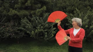 MS Elderly woman dancing with red fans