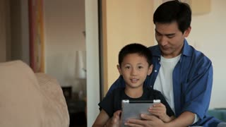 MS Father and son using digital tablet together in living room / China