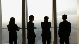 MS Four silhouettes of business people looking at city view, standing by office window / Beijing, China