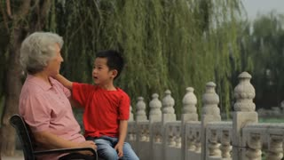 MS Grandmother talking with her grandson, sitting on park bench / China