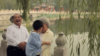 MS Grandparents laughing, carrying their grandson in a park/ Beijing, China