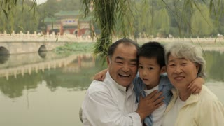 MS Grandparents laughing with their grandson in a park/ Beijing, China