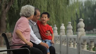 MS Grandparents sitting with their grandson on park bench / China