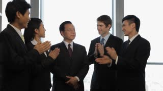 MS Group of business people clapping, standing around senior business man in office / China