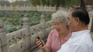 MS HA Elderly couple talking on mobile phone in a park/ Beijing, China