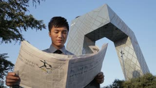 MS LA Young man reading newspaper, CCTV Headquarters building in background / Beijing, China
