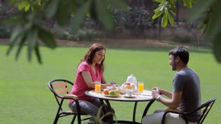MS Man and woman have breakfast in backyard / India
