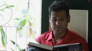 MS Man reading book, smiling and looking through window