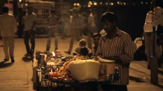 MS Man selling food from cart on street at night / India