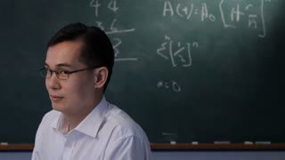 MS Man taking off glasses and smiling, in front of blackboard
