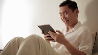 MS Mid-adult man using tablet pc on sofa / Singapore
