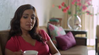 MS Mid-adult woman drinking coffee in living room / India