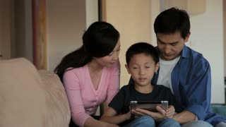 MS Mother, father and son using digital tablet in living room / China