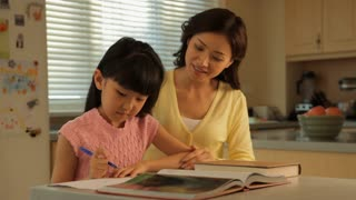 MS Mother helping daughter with homework in kitchen / China