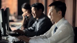 MS Office workers typing in office, young man turning and smiling towards camera / China
