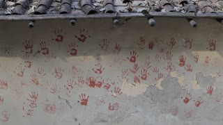 MS Painted handprints on side of house / India